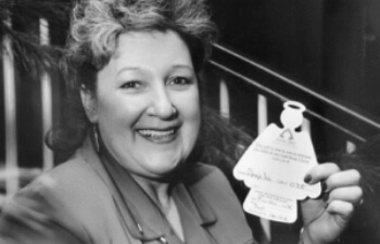 Photo of Mary Kay Beard, the founder of Angel Tree, holding an angel-shaped gift tag