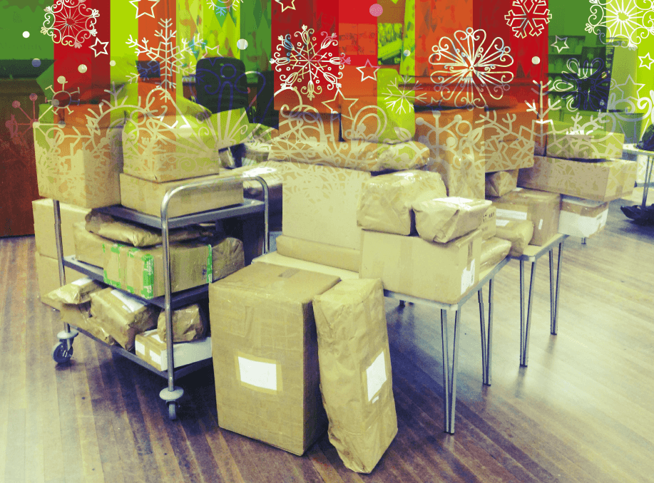 Photo of dozens of wrapped presents piled up on a table ready to be sent to children.